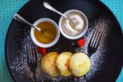 Rysk sirniki f?r sunda frukoststugaostkakor med honung och gr?ddfil f?r frukost p? bl? bakgrund arkivfoton
