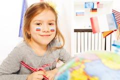 Rysk skolflicka som lär geografi på gruppen royaltyfri foto