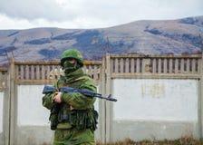 Rysk soldat som bevakar en ukrainsk sjö- grund i Perevalne, C Arkivfoton