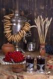 Rysk traditionell kokkärlsamovar på trätabellen Svart te, baglar, röd viburnum-, driftstopp- och rysssamovar i den lantliga vagel Royaltyfri Foto