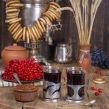 Rysk traditionell kokkärlsamovar på trätabellen Svart te, baglar, röd viburnum-, driftstopp- och rysssamovar i den lantliga vagel Royaltyfri Fotografi