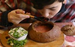 Rysk traditionell kokkonst - röd rödbetasoppa för borsch med sourcream och dill i bondaktigt stilbröd för rund råg royaltyfria foton