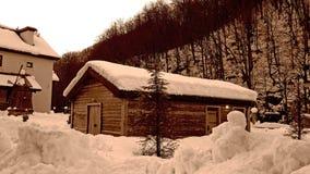 Rysk vinter, trähus och väderkvarn i snön Royaltyfri Foto