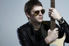Rysk vippa Grabben med gitarren som är främst av en fotograf Grungemusik, rader, musik, instrument, gitarr, andlighet Arkivfoton