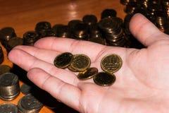 Ryska mynt i hand på gömma i handflatan mot bakgrunden av staplade mynt royaltyfri bild