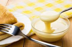 Ryska pannkakor i platta, gaffel och bunke med förtätat mjölkar Royaltyfri Fotografi