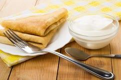 Ryska pannkakor i platta, gaffel och bunke med gräddfil Royaltyfri Fotografi