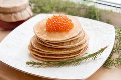 Ryska pannkakor med den röda kaviaren på plattan Arkivbild