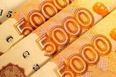 Ryska pengarsedlar med störst värde 5000 rubel stänger sig upp Makro som skjutas av orange sedlar Royaltyfri Foto
