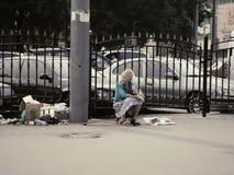 Ryska pensionärer - dåligt klädd gammal kvinna på gatan som hawkering nära avskräde Royaltyfri Foto