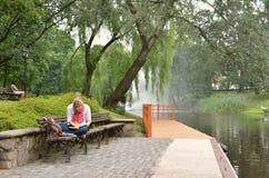 RYSKI, LATVIA, Lipze/- 27, 2013: Młoda kobieta pisze coś w jej notatniku na brzeg rzeki w miasto parku Ryski obraz royalty free
