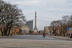 RYSKI, LATVIA, LISTOPAD - 14, 2018: Latvia 100 rok Pedestrians i ruch drogowy przy wolność zabytkiem w centrum miasta zdjęcie stock