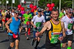 Ryski, Latvia, Maj - 19 2019: Kaukaski m?ski maratonu biegacz pokazuje aprobaty zdjęcie stock