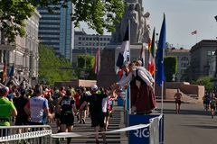 Ryski, Latvia, Maj - 19 2019: Marato?scy biegacze dosi?ga wolno?ci statu? z tradycjonalnie okrytymi cheerleaders daj? wysokim pis zdjęcia stock