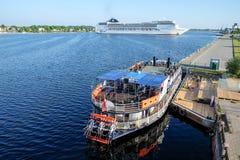 Ryski, Latvia, Maj - 21, 2016: Statku Wycieczkowego MSC opera obraca round i Turystyczną rzeczną łódź z paddle kołem miast embank Obrazy Stock