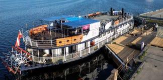 Ryski, Latvia, Maj - 21, 2016: Turystyczna rzecznej łodzi perła Ryski z paddle kołem miasta embankement - Rigas perła - Obrazy Stock