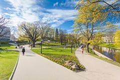 RYSKI, LATVIA, MAJ - 06, 2017: Widok na drogach przemian z okwitnięć drzewami, krzaki i odprowadzeń ludzie w Parkowym bastionie C Fotografia Stock
