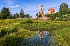 Ryskt landskap med den lilla stillsamma floden och den gamla kyrkan Arkivbild