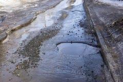 Rysligt dålig asfaltstadsväg med en grop och en pöl royaltyfria bilder
