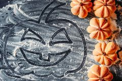 Rysować Halloweenowej bani na mąki tle i domowej roboty ciastkach obrazy royalty free
