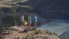 Ryssland Altay 13 august 2017 Den turist- gruppen tycker om den härliga bergfloden och bra väder överst av klippan Arkivfoto