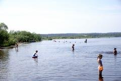 Ryssland - Berezniki Juli 18: ungdomarhoppar in i floden på solnedgången Royaltyfri Fotografi