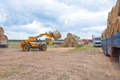 RYSSLAND BRYANSK-SEPTEMBER 6: Lantligt landskap med jordbrukmaskinerna på September 6,2014 i Bryanskaya Oblast, Ryssland Arkivfoton