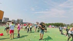 RYSSLAND IRKUTSK - JUNI 27, 2018: Lyckliga ungdomarsom dansar och firar under den Holi festivalen av färger Folkmassa av stock video