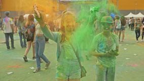 RYSSLAND IRKUTSK - JUNI 27, 2018: Lyckliga ungdomarsom dansar och firar under den Holi festivalen av färger Folkmassa av lager videofilmer