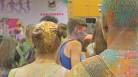 RYSSLAND IRKUTSK - JUNI 27, 2018: Lyckliga ungdomarsom dansar och firar under den Holi festivalen av färger Folkmassa av arkivfilmer