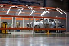 Ryssland Izhevsk - December 15, 2018: LADA Automobile Plant Izhevsk Den kvinnliga arbetaren fixar en detalj på den nya bilen royaltyfria foton