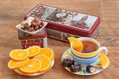 Ryssland Izhevsk - Maj 15, 2017: Teservisbergstopp Ceylon svart och kinesiskt grönt te Skivor av den nya apelsinen och sötsaker Royaltyfri Foto