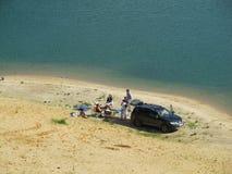 Ryssland Kazan - Juni 2011: ungdomarpå en picknick vid sjön arkivfoto