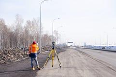 Ryssland Kemerovo 2019-03-15 Land- och konstruktionsinspekt?rutrustning Geodeten kontrollerar den robotic sammanlagda stationsteo royaltyfria foton