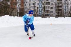 RYSSLAND KOROLEV- FEBRUARI 18, 2017: Den unga hockeyspelaren har en uppvärmningsutbildning för matchen på krokig turnering in Arkivfoto