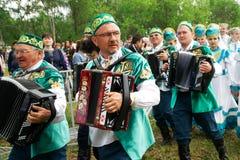 Ryssland Magnitogorsk, - Juni, 15, 2019 Dragspelare - deltagare av gatan ståtar i traditionella nationella dräkter under royaltyfria bilder