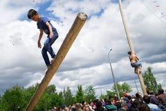 Ryssland Magnitogorsk, - Juni, 15, 2019 Grabbarna klättrar journalerna under Sabantuy - den nationella ferien av plogen royaltyfri fotografi