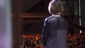 RYSSLAND MOSKVA - APRIL 13, 2019: Kvinnan ger föreläsning på etapp med åhörare konst Den lyckade kvinnan gör på anförande fotografering för bildbyråer
