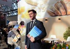 03 14 2019 Ryssland, Moskva att le mannen, i en affärsdräkt, står mot bakgrunden av en informationsställning med royaltyfri foto