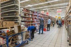 RYSSLAND MOSKVA, JUNI 11, 2017: Folk som shoppar för olika produkter i den Auchan supermarket Arkivfoto