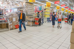 RYSSLAND MOSKVA, JUNI 11, 2017: Folk som shoppar för olika produkter i den Auchan supermarket Royaltyfri Foto