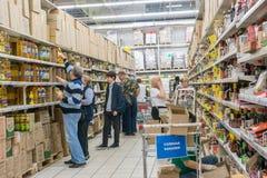 RYSSLAND MOSKVA, JUNI 11, 2017: Folk som shoppar för olika produkter i den Auchan supermarket Fotografering för Bildbyråer