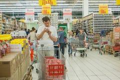 RYSSLAND MOSKVA, JUNI 11, 2017: Folk som shoppar för olika produkter i den Auchan supermarket Royaltyfri Fotografi