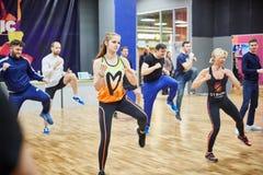 RYSSLAND MOSKVA - JUNI 03, 2017 grupp människor som utarbetar med steppers i idrottshall royaltyfri fotografi