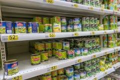 RYSSLAND MOSKVA, JUNI 11, 2017: Olik sort av på burk gröna ärtor på hyllorna i supermarket Auchan Arkivfoto