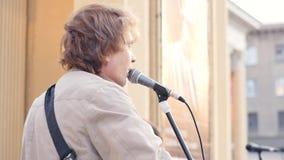 Ryssland Novosibirsk, April 2019: Gatamusiker spelar gitarrer och sjunger s?nger f?r passersby l?ngsam r?relse stock video