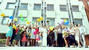 Ryssland Novosibirsk, 11 august 2017 Lyckliga bröllopgäster med brud- och brudgumbanhoppningen med ballonger after arkivfilmer