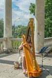 Ryssland Pavlovsk parkerar, Juli 22, 2017 flickan som harpisten utför i th Royaltyfri Fotografi