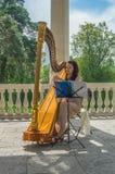 Ryssland Pavlovsk parkerar, Juli 22, 2017 flickan som harpisten utför på th Royaltyfri Foto