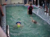 Ryssland Saratov - 12 Maj 2019: Barn idrottsman nen, simmare simmar längs spår i sportpölen för att simma Sportar som simmar i p? royaltyfri fotografi